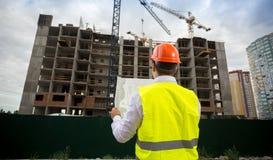 Foto der hinteren Ansicht des männlichen Architekten im Hardhat, der auf Baustelle steht und auf Plänen schaut stockfotos