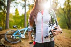 Foto der jungen sportlichen Frau mit Sturzhelm auf Hintergrund des Fahrrades am Herbstwald Lizenzfreies Stockfoto