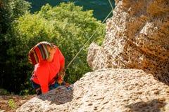 Foto der Klettererfrau in der Sonnenbrille, die oben nahe Berg schaut stockfotos