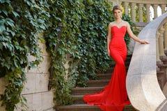 Foto der Mode im Freien der Schönheit trägt das luxuriöse Kleid und wirft im Sommerpark auf Landhaus ` s Treppe auf Stockfotos
