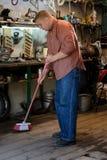 Foto der Reinigung des jungen Mannes und der ausgedehnten Garage Lizenzfreie Stockbilder