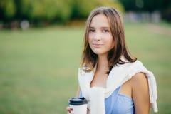 Foto der schönen comely Freundin mit weißer Strickjacke auf Schultern, Getränkmitnehmerkaffee, denkt an etwas, Stände übertreffen stockfoto
