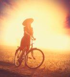 Foto der schönen jungen Frau auf Fahrrad auf dem wunderbaren sunse Lizenzfreies Stockfoto