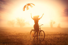 Foto der schönen jungen Frau auf Fahrrad mit Regenschirm auf dem w Lizenzfreies Stockbild