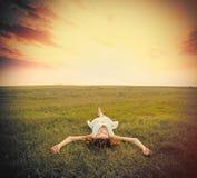 Foto der schönen jungen Frau, die auf dem Gebiet auf dem Himmel-BAC liegt Stockfoto