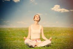 Foto der schönen jungen Frau, die joga tut und auf dem wo sich entspannt stockbild