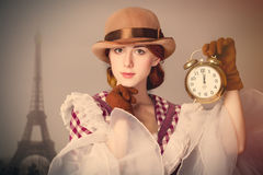Foto der schönen jungen Frau im Weinlesekleid mit Wecker Stockfotos