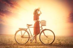 Foto der schönen jungen Frau mit Fahrrad auf der wunderbaren Sonne Stockbilder