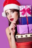 Foto der schönen jungen Frau mit Geschenken in Weihnachtsmann-Hut an Stockfoto
