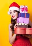 Foto der schönen jungen Frau mit Geschenken in Weihnachtsmann-Hut an Stockfotografie