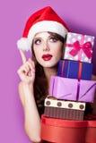 Foto der schönen jungen Frau mit Geschenken in Weihnachtsmann-Hut an Lizenzfreie Stockfotos