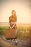 Foto der schönen jungen Frau mit Koffer auf der Straße nahe FI Stockbild