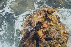 Foto der schönen klaren Seeozean-Wasseroberfläche mit Kräuselungen und des hellen Spritzens auf Steinmeerblickhintergrund Stockbilder