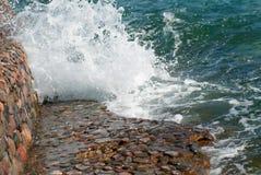 Foto der schönen klaren Türkisseeozean-Wasseroberfläche mit Kräuselungen und des hellen Spritzens auf Steinmeerblickhintergrund Lizenzfreies Stockbild