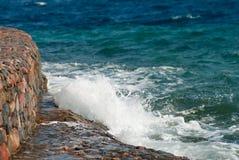 Foto der schönen klaren Türkisseeozean-Wasseroberfläche mit Kräuselungen und des hellen Spritzens auf Steinmeerblickhintergrund Lizenzfreie Stockbilder