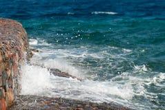Foto der schönen klaren Türkisseeozean-Wasseroberfläche mit Kräuselungen und des hellen Spritzens auf Steinmeerblickhintergrund Stockfotos