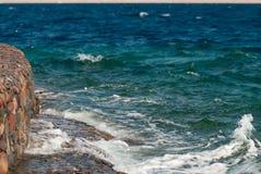Foto der schönen klaren Türkisseeozean-Wasseroberfläche mit Kräuselungen und des hellen Spritzens auf Steinmeerblickhintergrund Stockfotografie