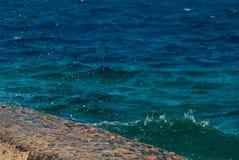 Foto der schönen klaren Türkisseeozean-Wasseroberfläche mit Kräuselungen und des hellen Spritzens auf Steinmeerblickhintergrund Lizenzfreies Stockfoto