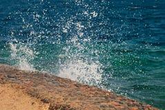 Foto der schönen klaren Türkisseeozean-Wasseroberfläche mit Kräuselungen und des hellen Spritzens auf Steinmeerblickhintergrund Lizenzfreie Stockfotos