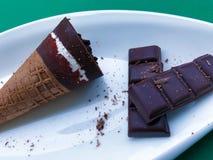 Foto der SchokoladenEiscreme in den Waffelkegeln Gedient auf weißer Platte auf grünem Hintergrund mit dunkler Bitterschokolade lizenzfreie stockbilder
