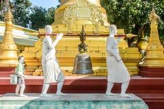 Foto der Statue, kupferne Glocke trägt durch whiterobed Diakon, c stockbilder