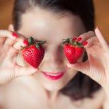 Foto der verlockenden weiblichen haltenen Erdbeere nahe Gesicht eyeys, beißende Beere der sinnlichen Frau der Nahaufnahmeporträtr lizenzfreie stockfotos