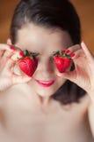 Foto der verlockenden weiblichen haltenen Erdbeere nahe Gesicht eyeys, Cl lizenzfreie stockfotografie