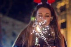 Foto der Wunderkerze mit Frau im Hintergrund Glückliches neues Jahr Stockbilder