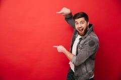 Foto des aufgeregten Mannes mit Bart in der Freizeitbekleidung das Fing zeigend stockfoto