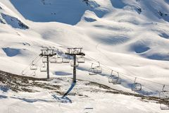 Foto des Drahtseilbahnausschnitts unter schneebedeckten Hügeln lizenzfreies stockbild