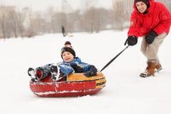 Foto des Eislaufsohns des netten Vaters auf Schläuche am Winternachmittag Stockfotografie