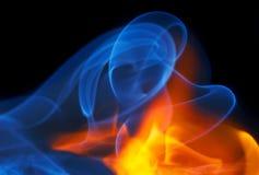Foto des Feuers mit einem Rauche auf einem schwarzen Hintergrund lizenzfreies stockbild