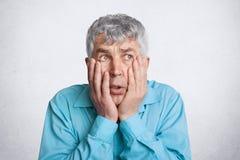 Foto des frustrierten grauen behaarten Mannes der Unzufriedenheit, hält Hände auf Backen, schaut hoffnungslos irgendwo, trägt for Stockbild