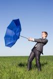 Foto des Geschäftsmannflugwesens auf seinem Regenschirm Stockfotos