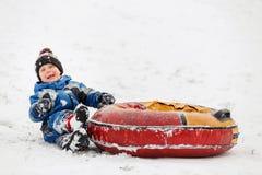 Foto des glücklichen Jungen mit Schläuche im Winterpark Stockfoto