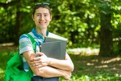 Foto des glücklichen Mannes mit Laptop, Bücher Lizenzfreie Stockfotos