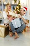 Foto des glücklichen Mannes und der Frau in Sankt-Kappe mit Geschenk im Kasten Stockfoto