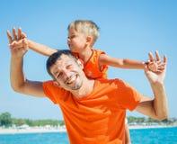 Foto des glücklichen Vaters und des Sohns auf dem Strand Stockfotografie