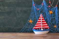Foto des hölzernen Segelboots vor Tafel mit Seeillustrationen Lizenzfreie Stockfotografie