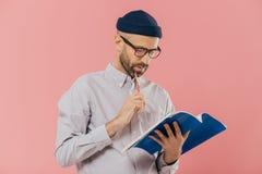 Foto des hübschen männlichen Autors hat dunkle Borste, hält Bleistift und Buch, unterstreicht notwendige Informationen, über rosa stockfoto