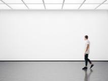 Foto des Hippies in der modernen Galerie, die das leere Segeltuch betrachtet Leeres Modell, Bewegungsunschärfe Lizenzfreies Stockbild