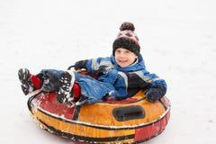 Foto des Jungen auf Schläuche im Winterpark Lizenzfreie Stockfotografie