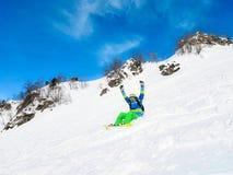 Foto des jungen Mannes im Sturzhelm und mit dem Snowboard, der auf Berghang liegt Stockfotos