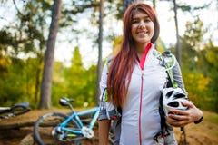 Foto des jungen sportlichen Brunette mit Sturzhelm auf Hintergrund des Fahrrades Stockbilder