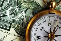 Foto des kanadischen Geldes und des Messing-Kompassses