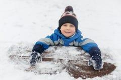 Foto des kleinen Jungen im Schnee auf Park Stockfotos