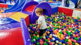 Foto des kleinen Jungen voll spielend im Pool von colroful Plastikb?llen Kleinkind, das Spa? auf Spielplatz im Einkaufen hat lizenzfreie stockfotografie