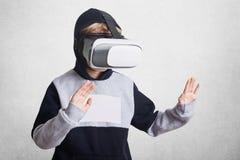 Foto des kleinen Kindes trägt virtuelle relality Schutzbrillen, erfährt aufgeregtes etwas, gestikuliert, sich unterhält Kind in V Lizenzfreies Stockbild
