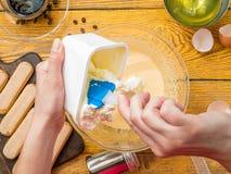 Foto des Kochs mit der Kelle, die Tiramisu zubereitet Lizenzfreies Stockfoto
