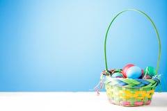 Foto des Korbes mit bunten Eiern auf leerem blauem Hintergrund Lizenzfreie Stockfotos